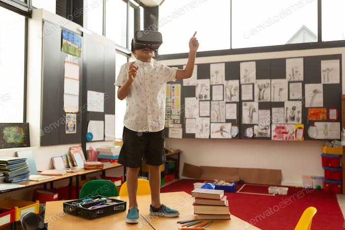 Schuljunge mit Virtual Reality Headset, während auf einem Schreibtisch im Klassenzimmer in der Schule stehen