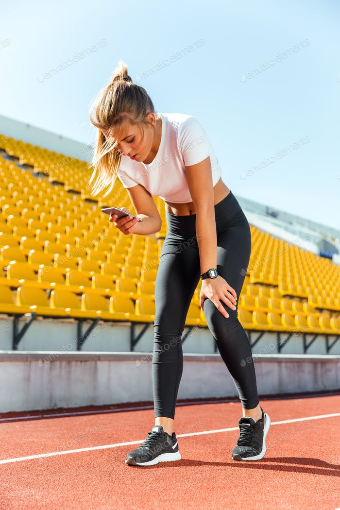 Woman resting after run and using smartphone