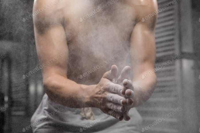 Mid section of shirtless man clapping hands with talc at the crossfit gym