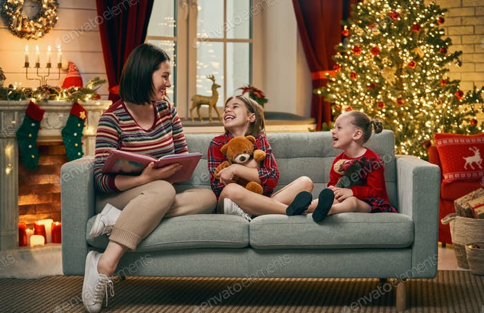 mother reading to daughters near Christmas tree.
