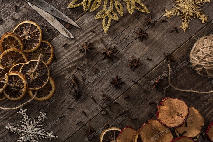 Dried Citrus And Apple Slices Near Snowflakes, Scissors, Thread And Anise on Wooden Surface