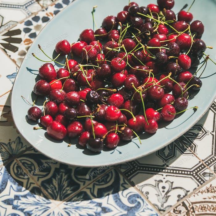 Fresh ripe sweet cherries in plate over oriental ceramic background