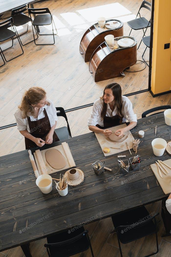 Mujeres que hacen cerámica de arcilla en la mesa con un instrumento de palo de madera y rodillo de madera