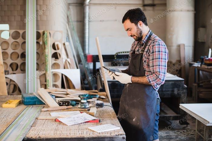 Porträt eines Zimmermann stehend in seinem Holzwerkstudio und hält digitale Tablette