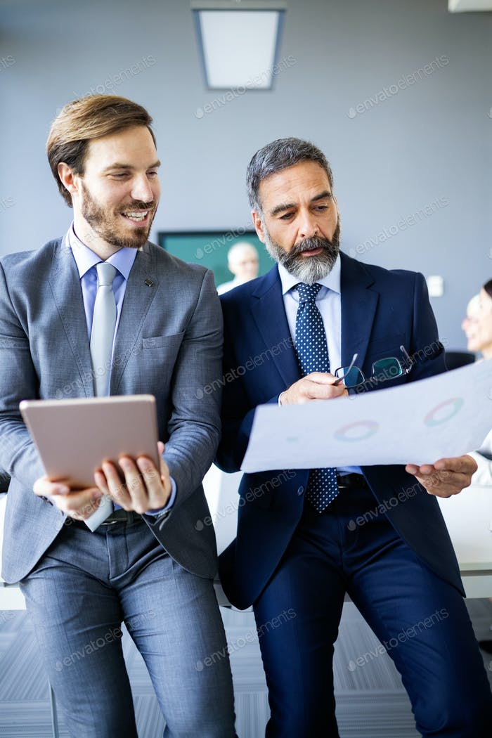 Mature businessman to discuss information with a younger colleague in a modern business office