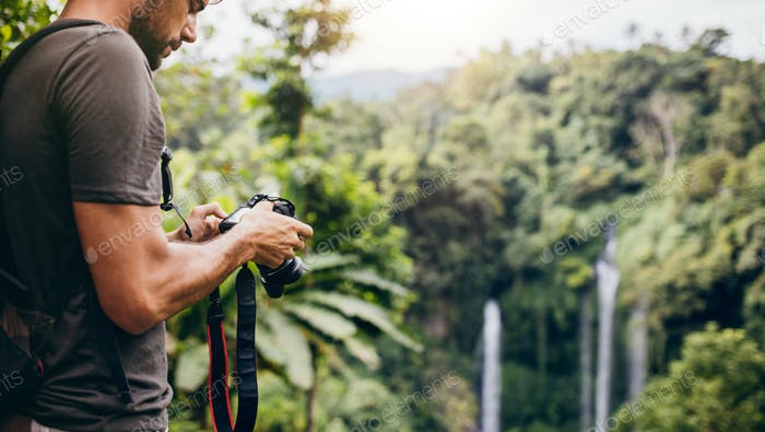 Young man with camera by a waterfall in forest