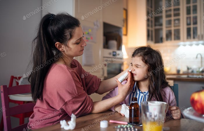 Mother looking after sick small daughter at home, using nasal spray