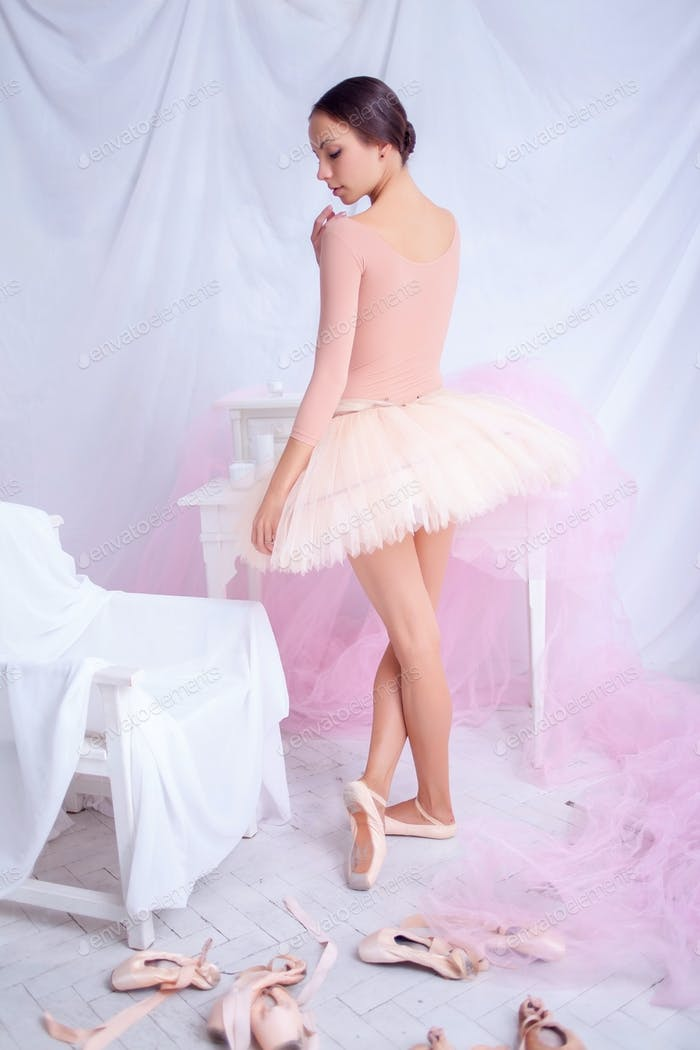 Professional ballet dancer posing on pink