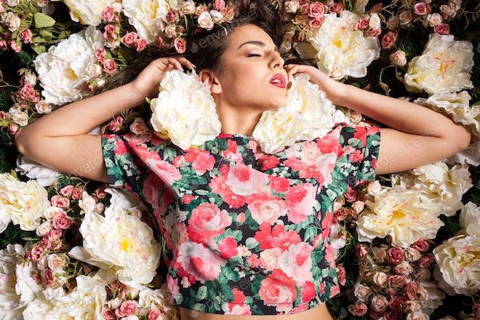 Schöne sinnliche Frau auf Blumen liegend