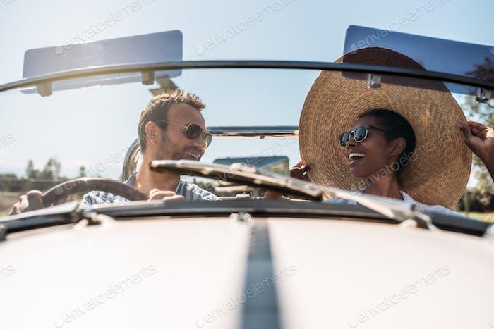Multiracial couple in a convertible vintage car