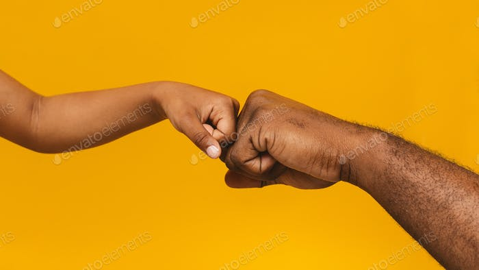 African man and little girl fist bump, close up