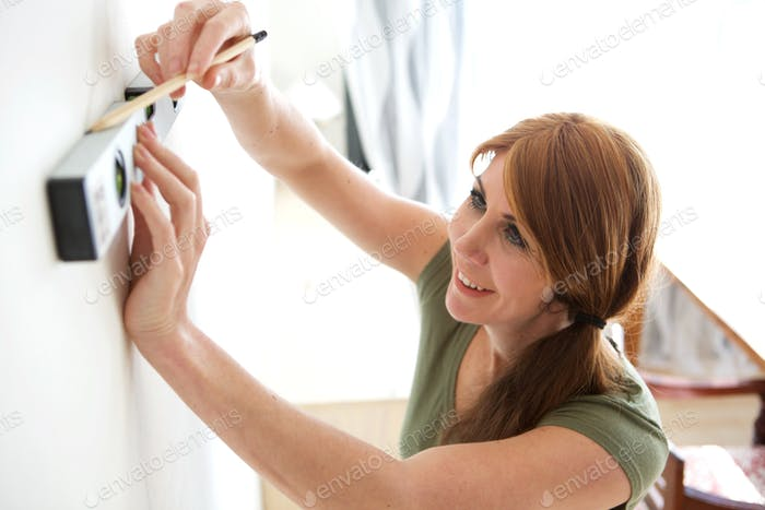 Woman using spirit level and pencil to mark the wall