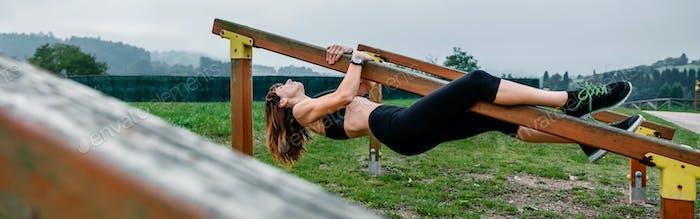 Тренировка спортсменки висит на деревянном брусе