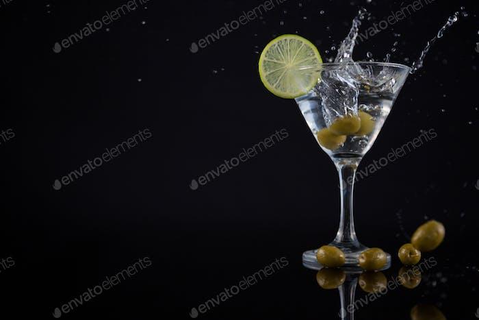 Olive spritzt zu einem Cocktail-Martini mit Limette auf dem Tisch