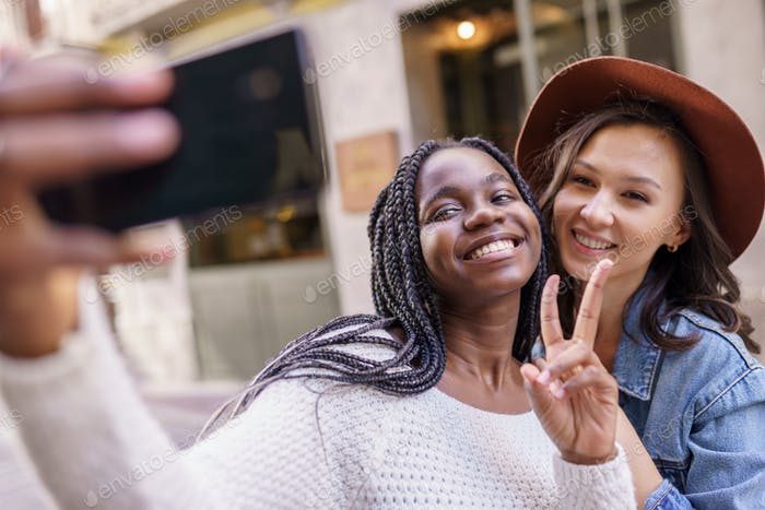Two beautiful multiethnic women making selfie and grimacing