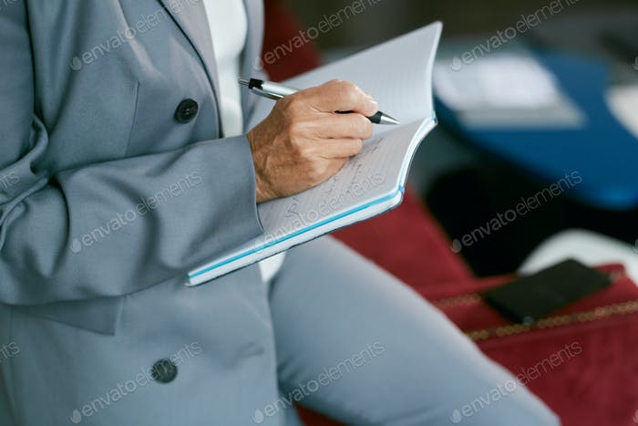 Businesswoman Writing in Note Book