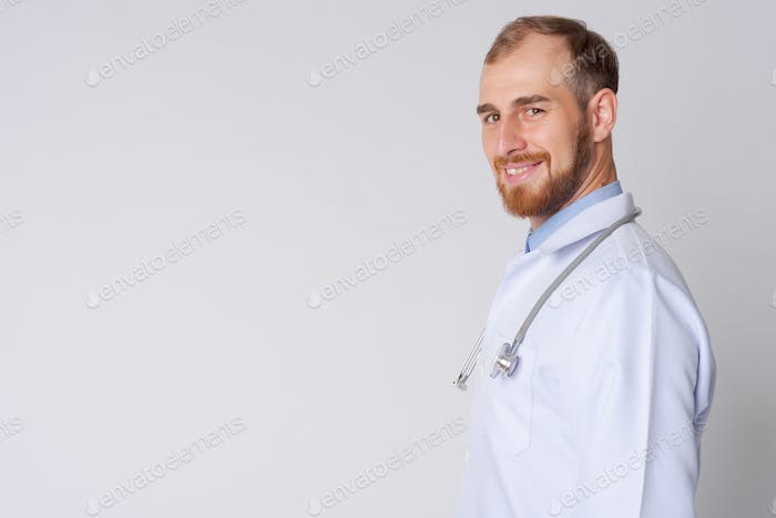 Profile view of happy young bearded man doctor looking at camera