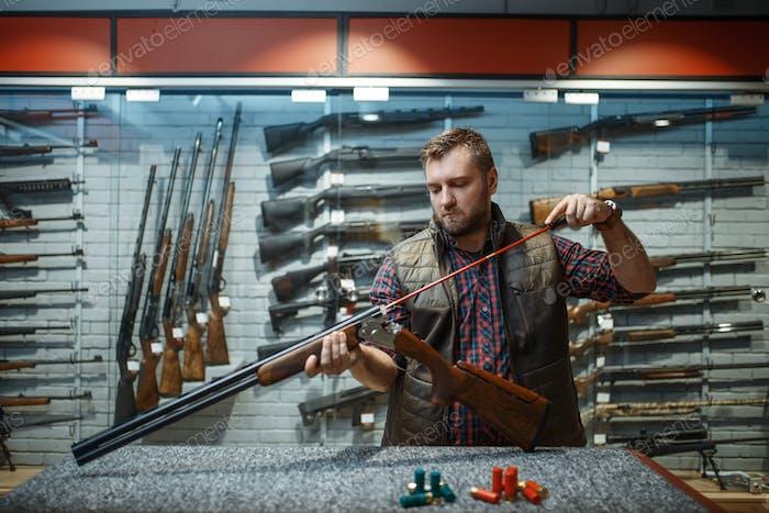 Man cleans rifle barrel at counter in gun shop
