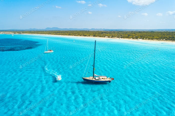 Aerial view of floating sailboat and motorboat in transparent sea