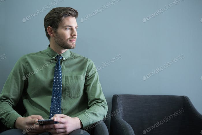 Male executive sitting with mobile phone in waiting area