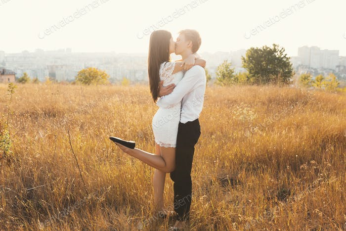 Loving couple dressed in white kissing outdoors, touching, gentl