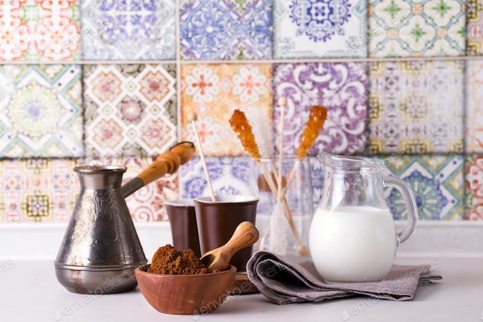 Grinded coffee in a wooden bowl with brown sugar stick on the background of a copper turks, milk and