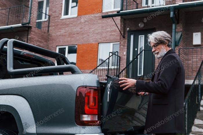 Fashionable senior man with gray hair and beard closes trunk of his car