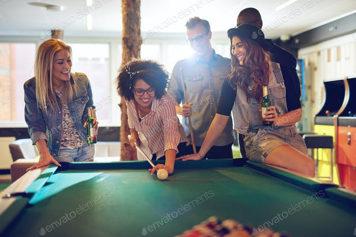 Woman behind the cue ball while friends watch
