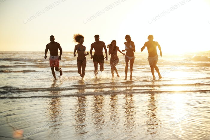 Group Of Friends Run Through Waves Together On Beach Vacation