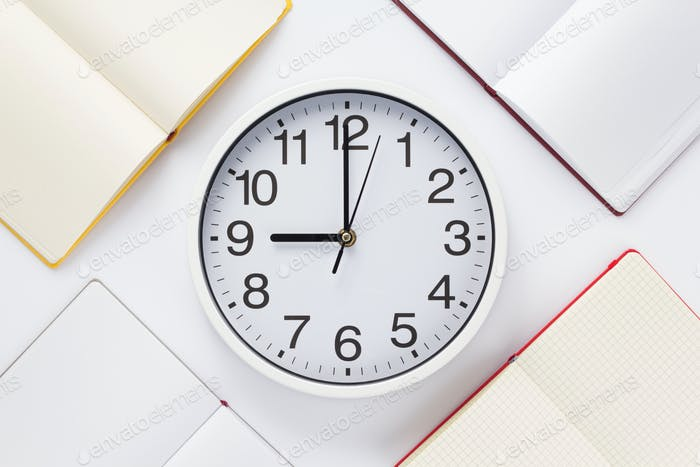 open notebook or book with wall clock