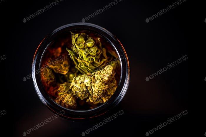 Cannabis Flower Buds in Glass Jar, Top Down Close Up. Dark Background. Medical Marijuana Concept