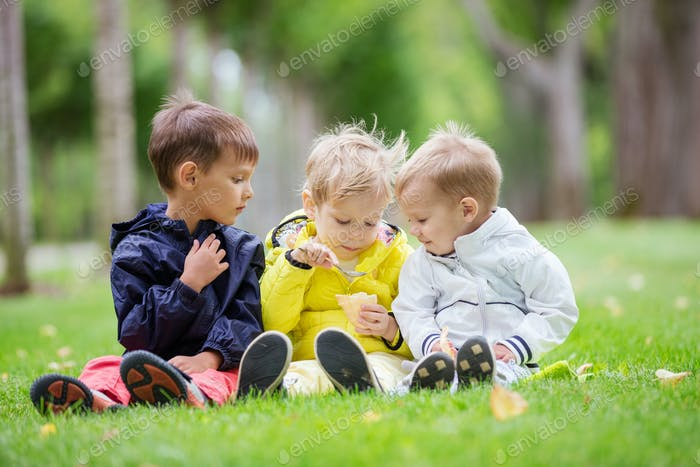 Young boys sitting on grass in park