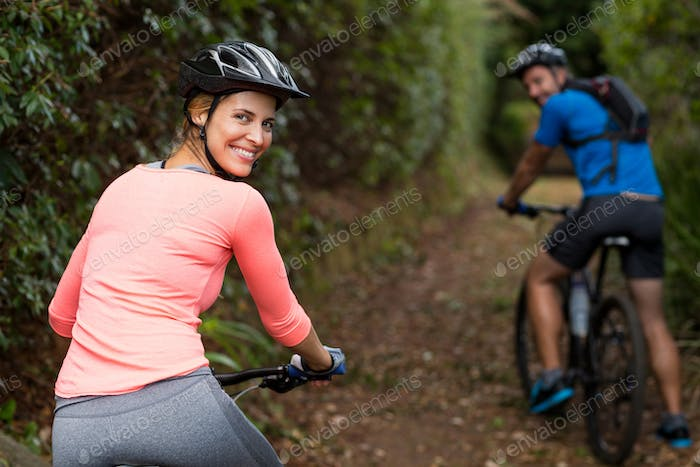 Athletic couple cycling in forest