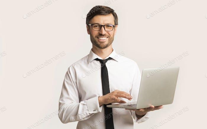 Erfolgreicher Mann Arbeiten auf Laptop stehend über weißem Hintergrund