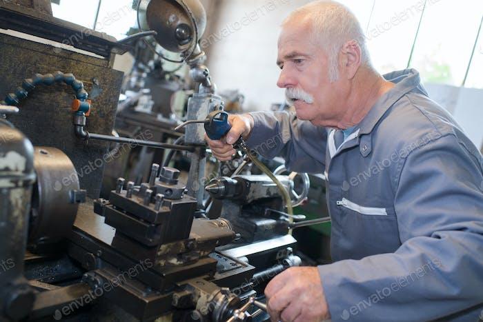 Senior Mann mit Luftleitung auf Maschinen