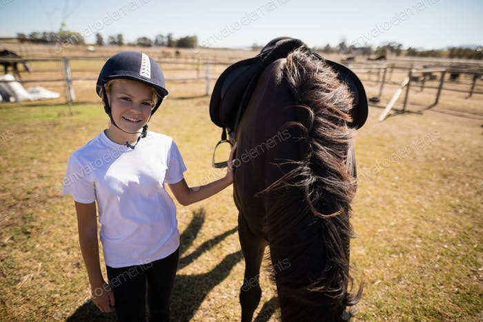 Smiling girl standing next to the brown horse in the ranch