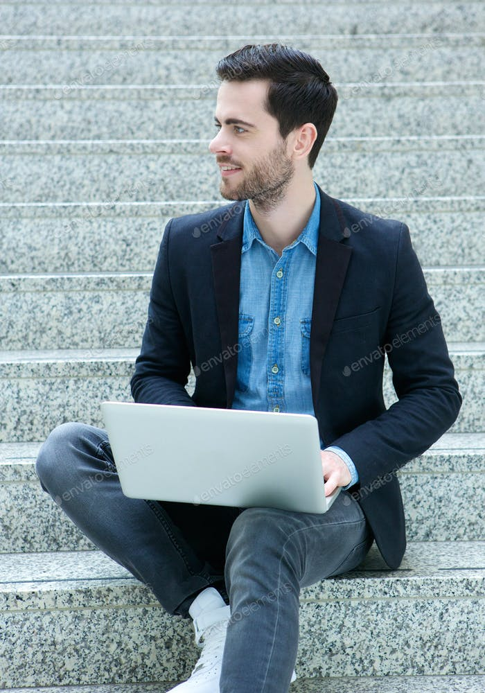 Young man sitting on steps with laptop