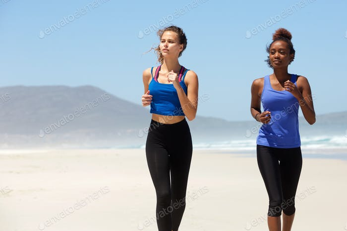 Two healthy young women running on the beach