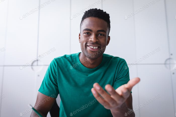 African american businessman sitting in office having video call and making notes