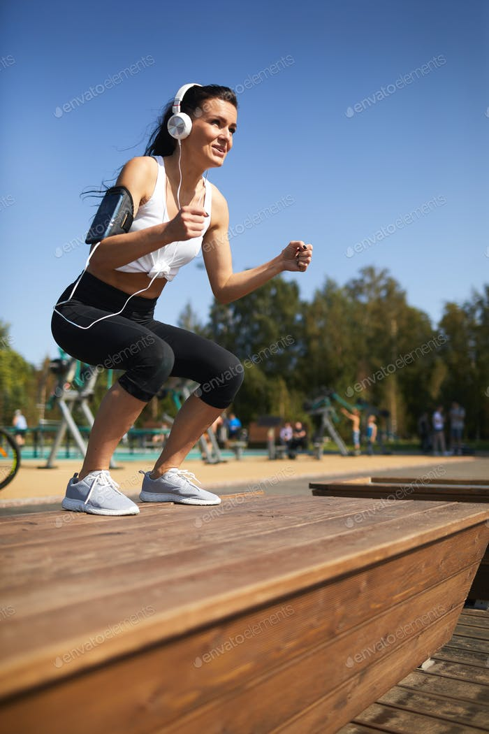 Cheerful woman in headphones doing jump squat on step