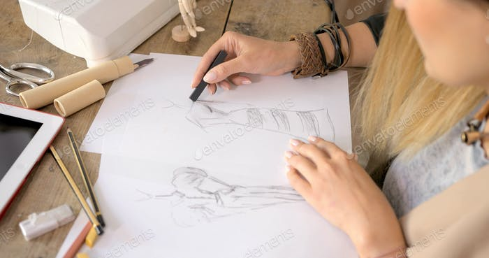 Crop shot of dressmaker drawing sketches