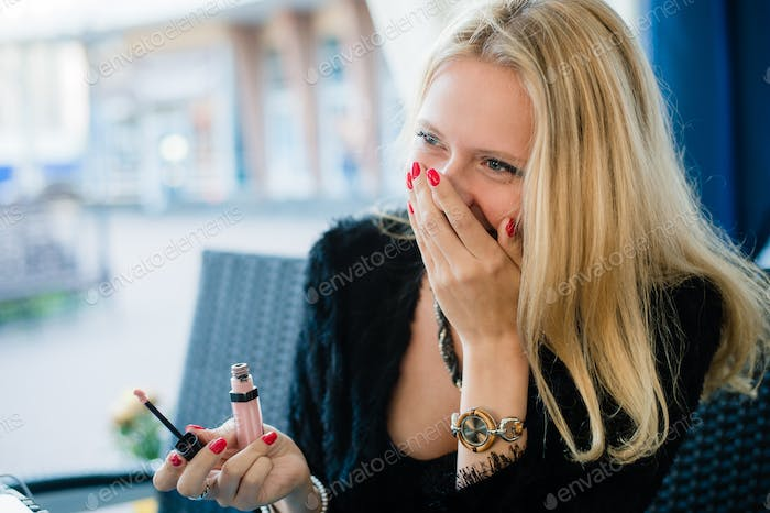 young beautiful blonde girl is sitting in a street cafe, posing fun laughing and smiling crazy woman