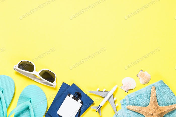 Blue flip flops, sunglasses, passport, plane and starfish on yellow background