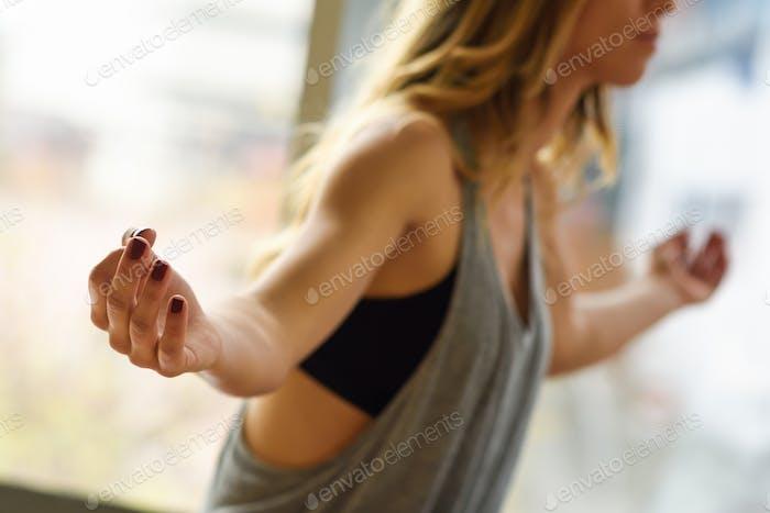 Junge schöne Frau meditiert in der Lotusposition im Fitnessstudio