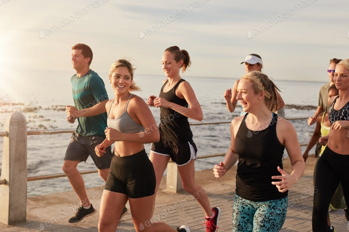 Healthy young people running together on seaside promenade