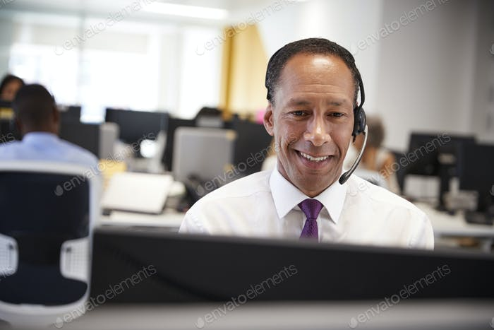 Middle aged man working at computer with headset in office