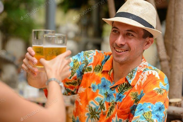 Glückliches Multi ethnischen Touristenpaar trinken Bier zusammen im Restaurant