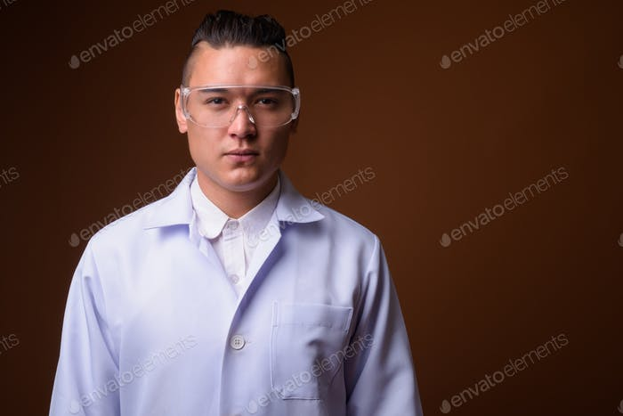 Young handsome multi-ethnic man doctor against brown background