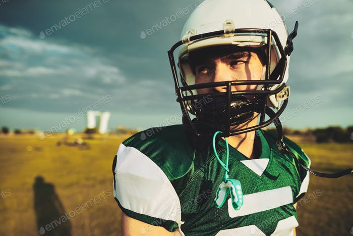 Young American football player standing alone on a field