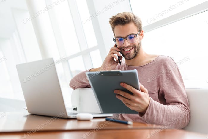 Image of man talking on cellphone and holding clipboard in cafe